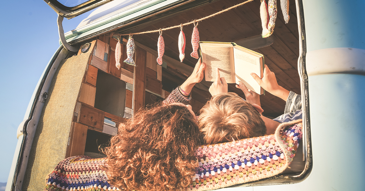 Mom and son travelling on mini-van reading book